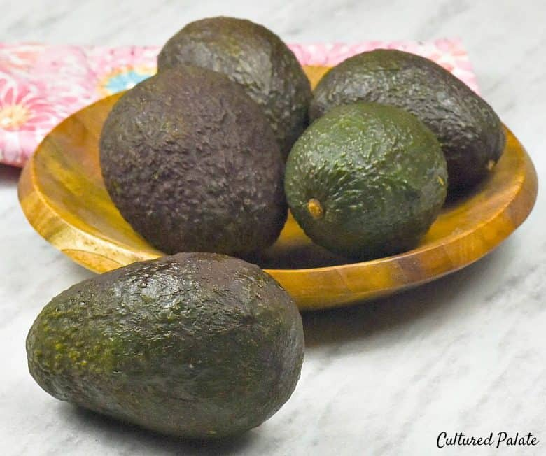 8 Health Benefits of Avocados - avocados shown in a wooden bowl