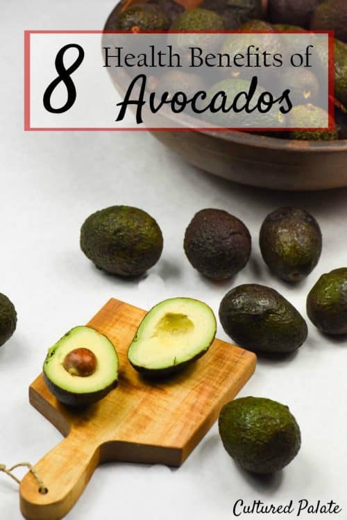 8 Health Benefits of Avocados - a photo of avocados on a wooden board and table.