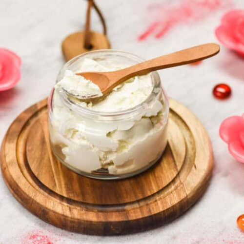 Whipped Body Butter Recipe made and shown in glass jar with candles and sppon