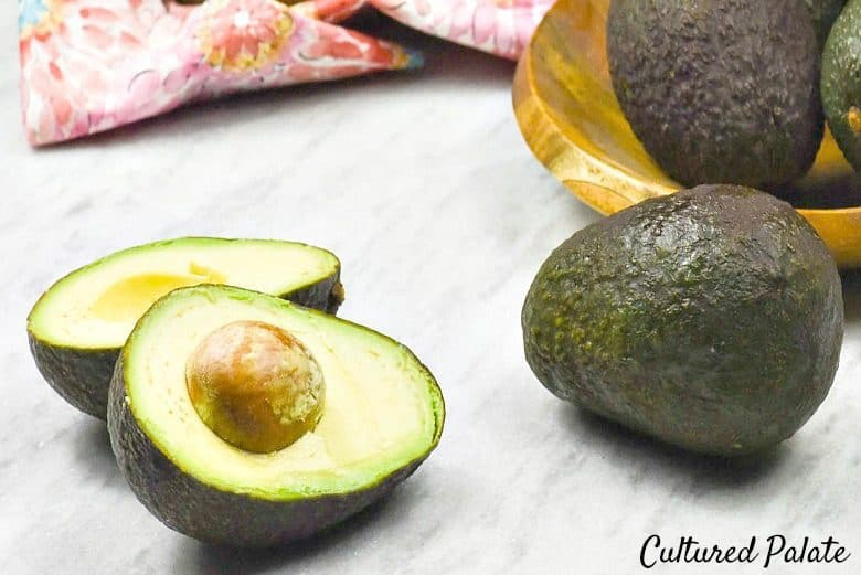 A horizontal photo of avocados on a table to show the health benefits of avocados.
