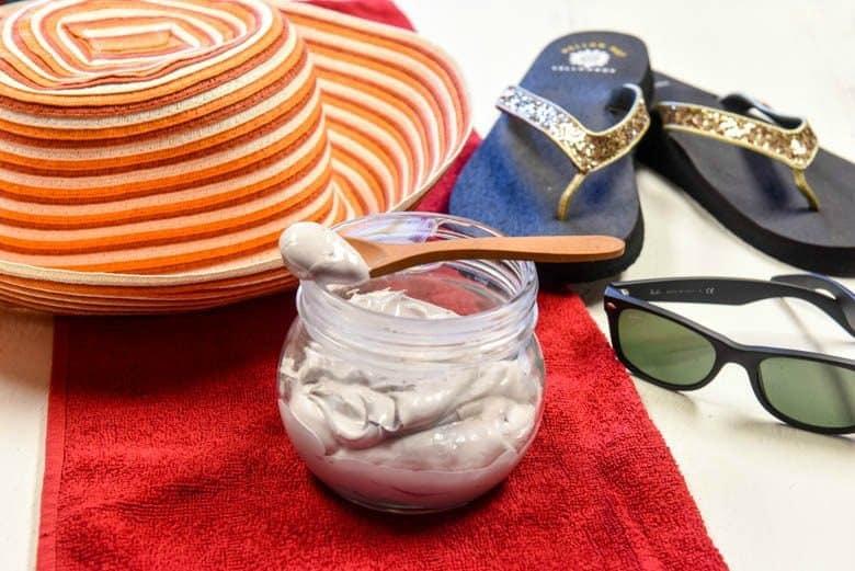 homemade sunscreen, DIY sunscreen shown with sun hat, beach towel, sunglasses and flip flops