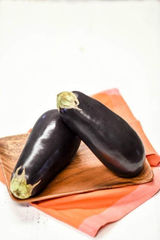 eggplant on white background with orange napkin - Health Benefits of Eggplant