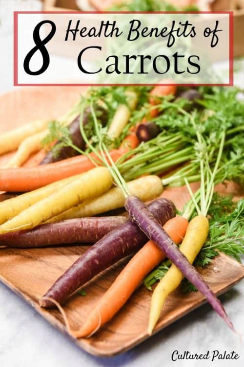 Purple, orange and yellow carrots shown on a wooden tray from the post, 8 Health Benefits of Carrots and post title at the photo top