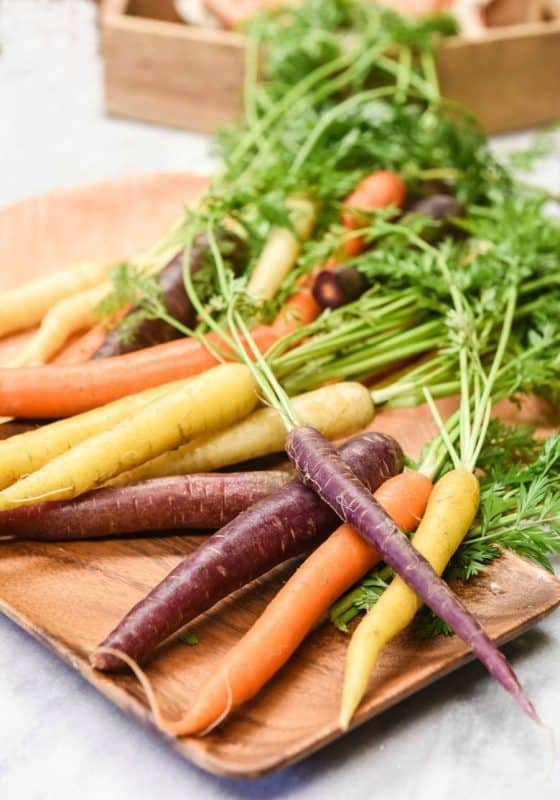 Purple, orange and yellow carrots shown on a wooden tray from the post, 8 Health Benefits of Carrots