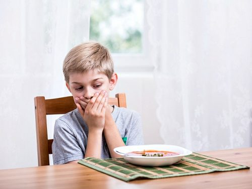 Young boy shown with hand over mouth - picky eaters