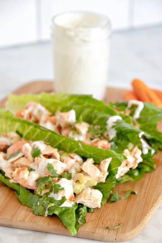 Vertical image showing Buffalo Chicken Lettuce Wraps on a cutting board with ranch dressing and carrots in the background