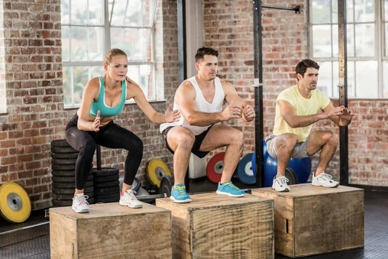 Fit people doing jump box in crossfit gym