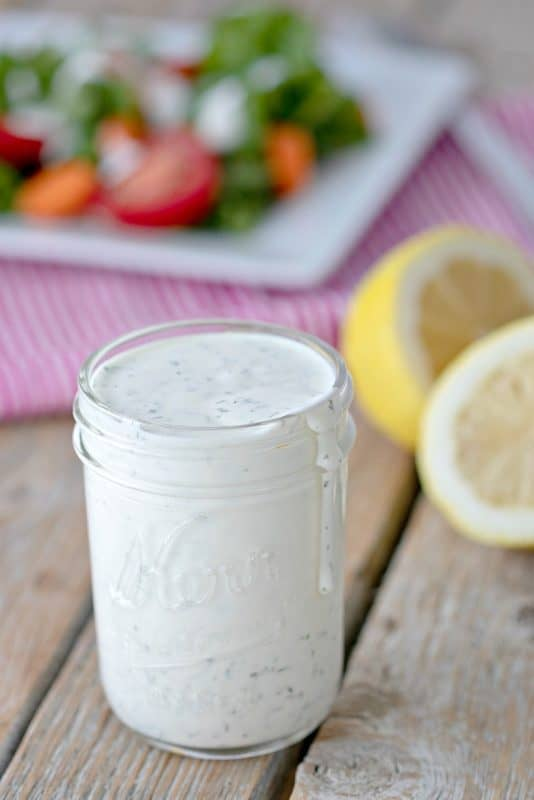 A mason jar of Homemade Ranch Dressing with lemons and veggies in the background