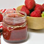 Jar of Instant Pot Strawberry Jam shown in front of a wooden bowl of fresh strawberries