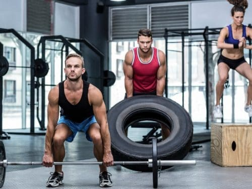 Three muscular athletes lifting and jumping at the crossfit gym from the post, What is CrossFit?