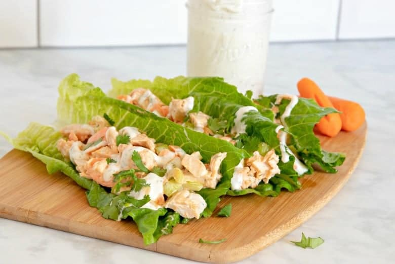 Buffalo Chicken Lettuce Wraps shown on a cutting board with homemade ranch in the background