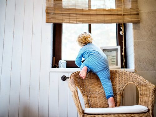 Image of little boy climbing on chair near a window to illustrate the importance of Childproofing - Home Safety for Children