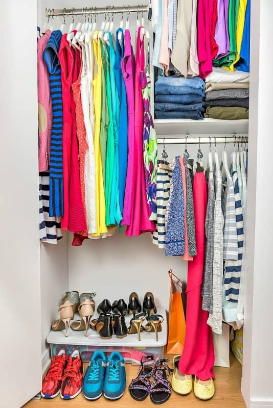 Vertical image of Clothes displayed neatly in a well organized closet. From the post How to Organize a Closet.