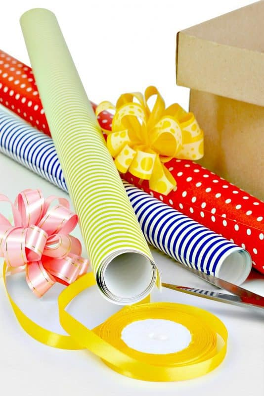 Vertical image of Gift wrap, ribbon, bows and box shown with scissors from the post Organizing Gift Wrap