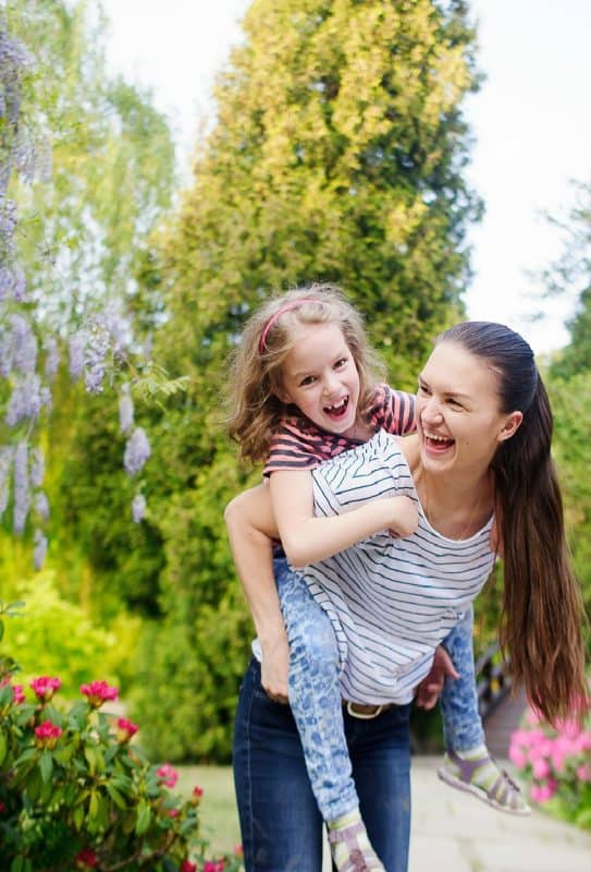 Vertical image of Mother and daughter shown having fun in the park from the post 7 Parenting Tips to Enjoy Your Child