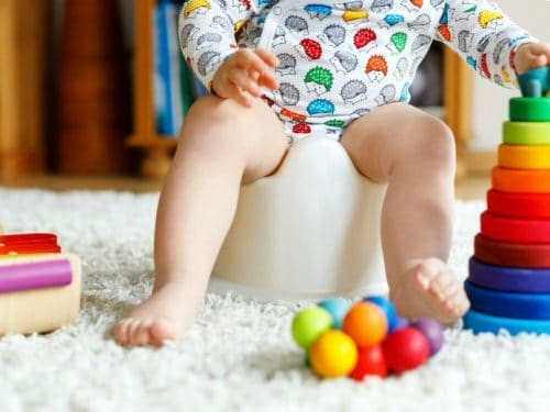 Toddler sitting on potty chair with brightly colored balls in front of him from the post Potty Training Tips
