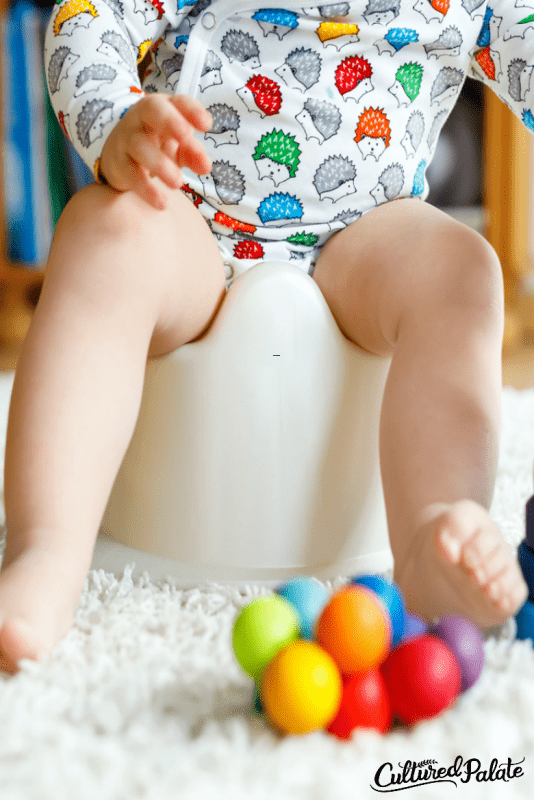 Vertical image of Toddler sitting on potty chair with brightly colored balls in front of him from the post Potty Training Tips