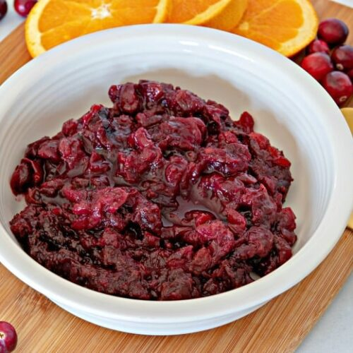 Horizontal image of a bowl of cranberry sauce on a wooden cutting board with cranberries and orange slices around it.