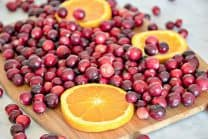 Ingredients for Cranberry Sauce recipe shown on wooden cutting board - cranberries and orange slices