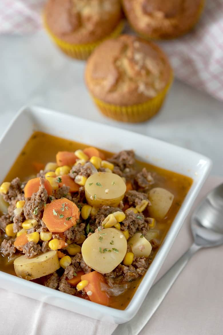 Vertical image of Instant Pot Beef Stew in a white square bowl with muffins in the background.