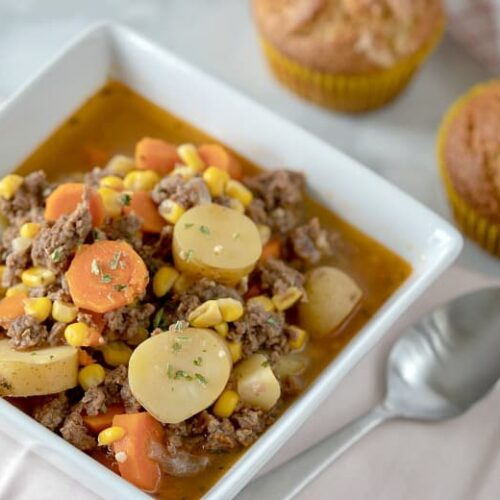Instant Pot Beef Stew shown in a white bowl with muffins in the background.