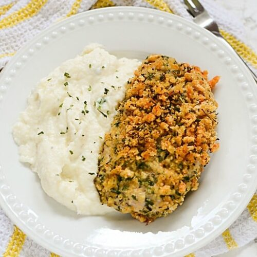 Horizontal image of a breaded pork chop with cauliflower mashed potatoes on marble background