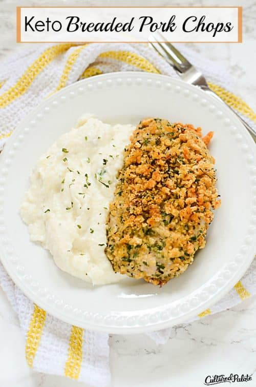 """Vertical image with the title """"Keto Breaded Pork Chops"""" showing breaded pork chop with mashed cauliflower on a white plate with yellow and white striped towel on marble background"""