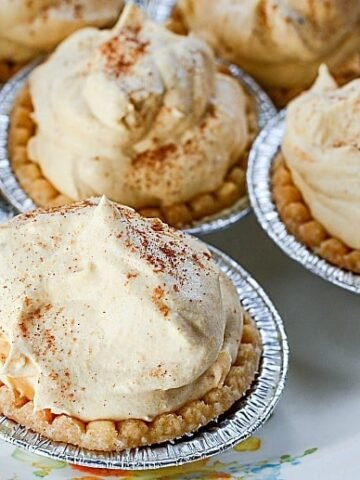Mini Pumpkin Pies shown on a white floral plate close up
