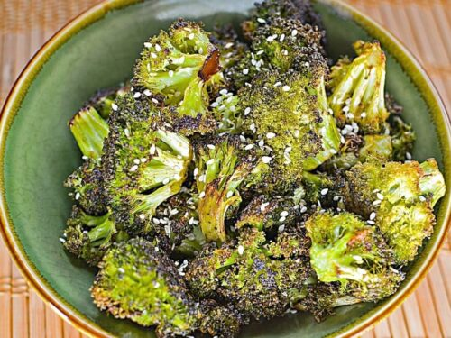 Sesame Oven Roasted Broccoli shown in a green bowl with sesame seeds on top