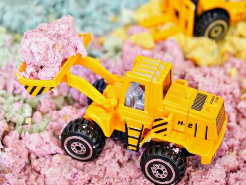 Pink moon sand with yellow tractor playing in it.