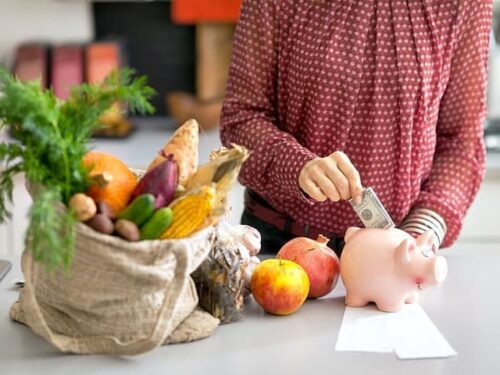 Woman putting money into a piggybank on a counter with fruits and veggies in a bag beside it from the post 10 Most Popular Money Saving Posts For 2018