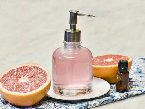 Homemade Body wash shown pink in a glass dispenser with two halves of grapefruit to either side