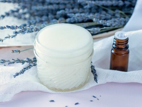 Best Sugar Scrub for Hands shown in glass jar with essential oil bottle and lavender in background