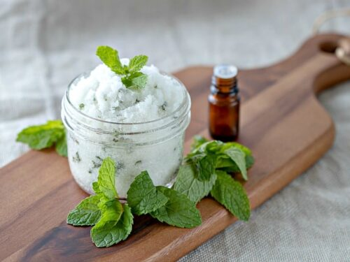 Mint Face Scrub shown in glass jar on cutting board with mint leaves around it.