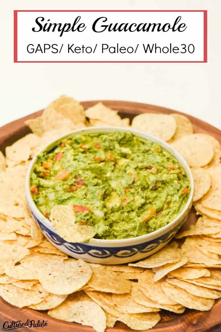 Vertical image of avocado dip from the Simple Guacamole Recipe shown in a bowl surrounded by chips on a wooden board