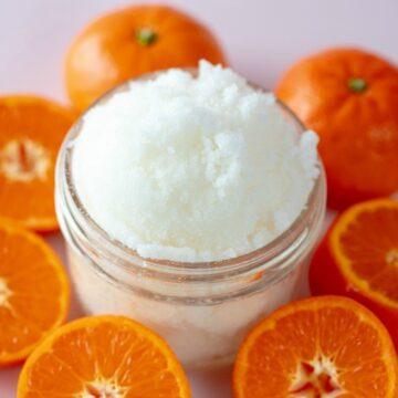 Wild Orange Sugar Scrub Recipe shown close up in glass jar with oranges around it.