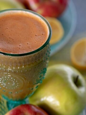 Carrot Celery Juice shown in glass with fruit around it.