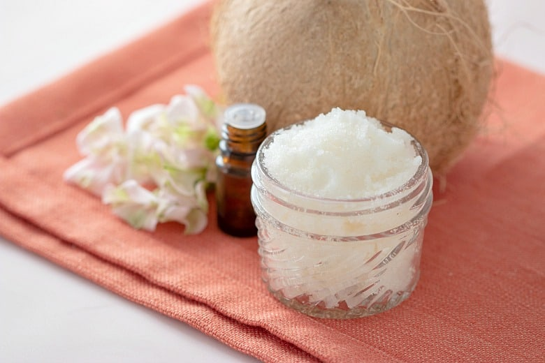 Coconut Body Scrub Recipe shown in glass jar with flowers, essential oils and coconut beside it.