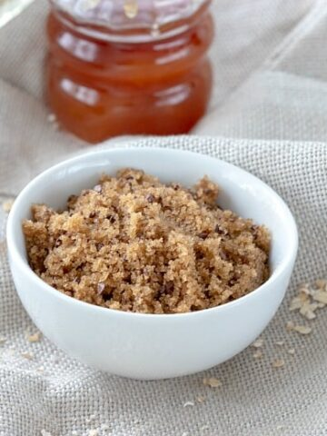 Face sugar scrub shown on linen tablecloth with oats around the bowl and honey and essential oils in background.