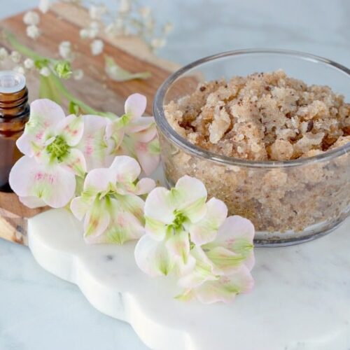 Homemade Sugar Exfoliating Scrub shown on marble cutting board with flowers to the side.