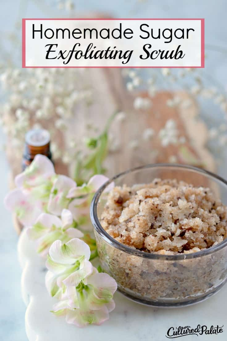 Homemade Sugar Exfoliating Scrub shown in glass jar with flowers, cutting board in background and text overlay.