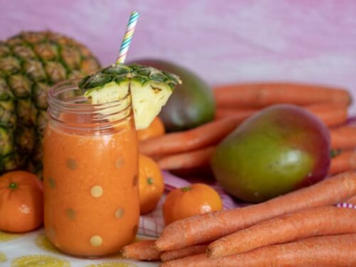Carrot Juice Recipe for Kids shown in glass jar with straw and fruit around