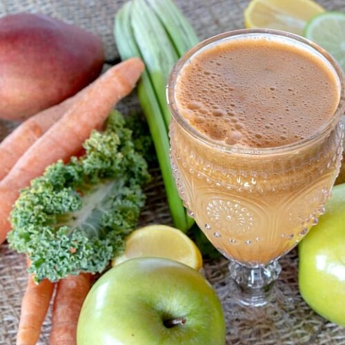 Green Carrot Juice Recipe shown with fruits and veggies around glass.
