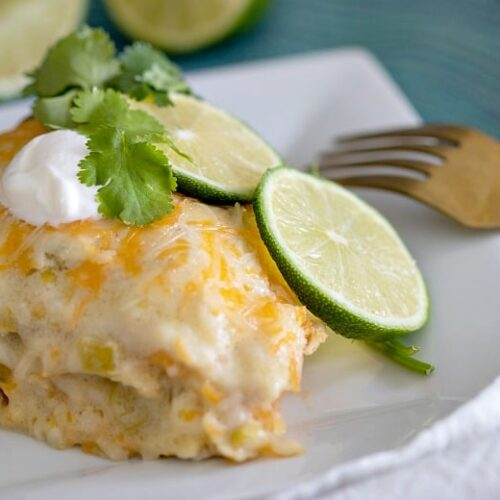 A piece of CrockpotWhite Chicken Enchilada Casserole on a white plate with fork to the side.