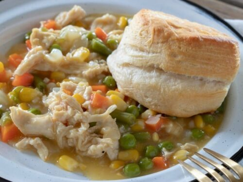 Crock Pot Chicken Pot Pie shown in horizontal image in white bowl with biscuit to side.
