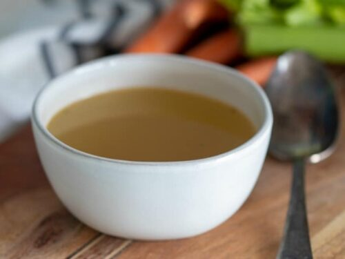 Crockpot Bone Broth shown on wooden table in a white bowl.