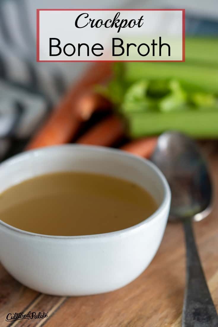 Vertical image of crockpot bone broth shown with vegetables in the background and spoon to the side of a white bowl.
