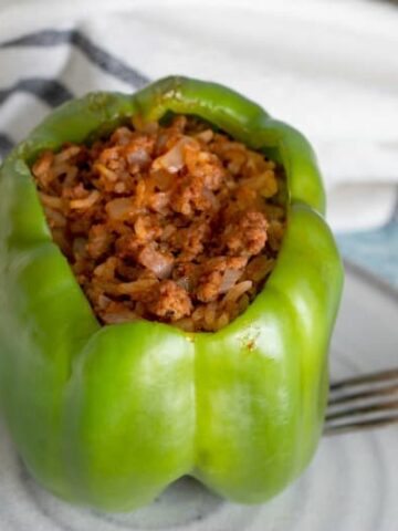 Stuffed pepper made in the crockpot shown from above on white plate.