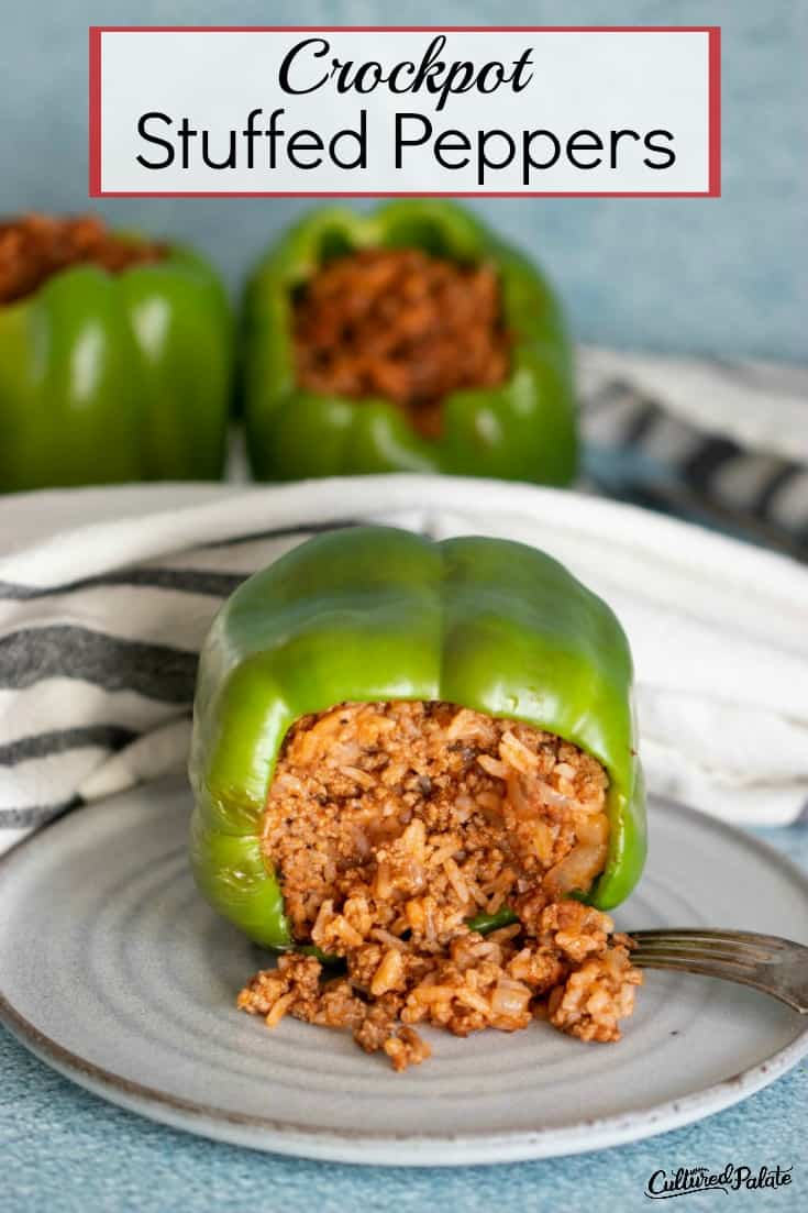 Stuffed pepper on its side with the filling spilling out onto a white plate.