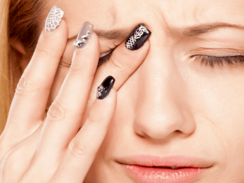 Horizontal image of a woman with fingers to her eye because of eye pain.